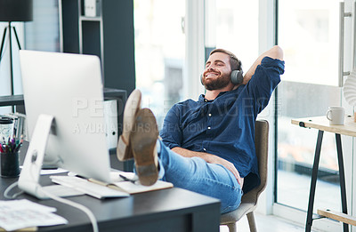Buy stock photo Shot of a happy young businessman using headphones while relaxing at her desk in a modern office