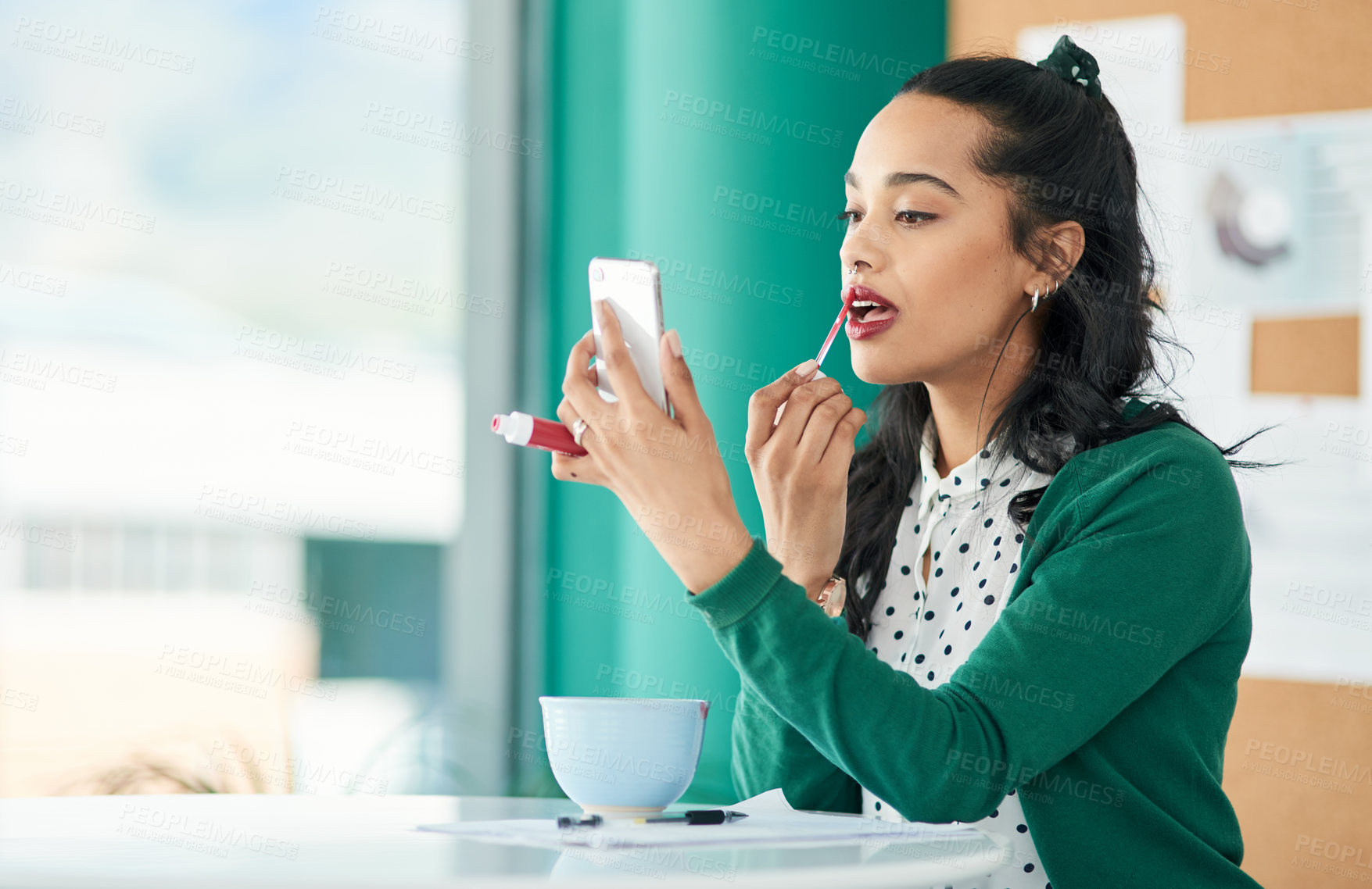 Buy stock photo Shot of a young businesswoman applying lipstick using a smartphone in a modern office