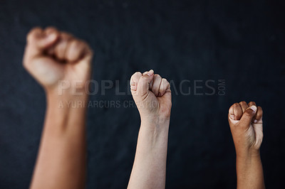 Buy stock photo Studio shot of a group of women raising their hands in solidarity against a dark background