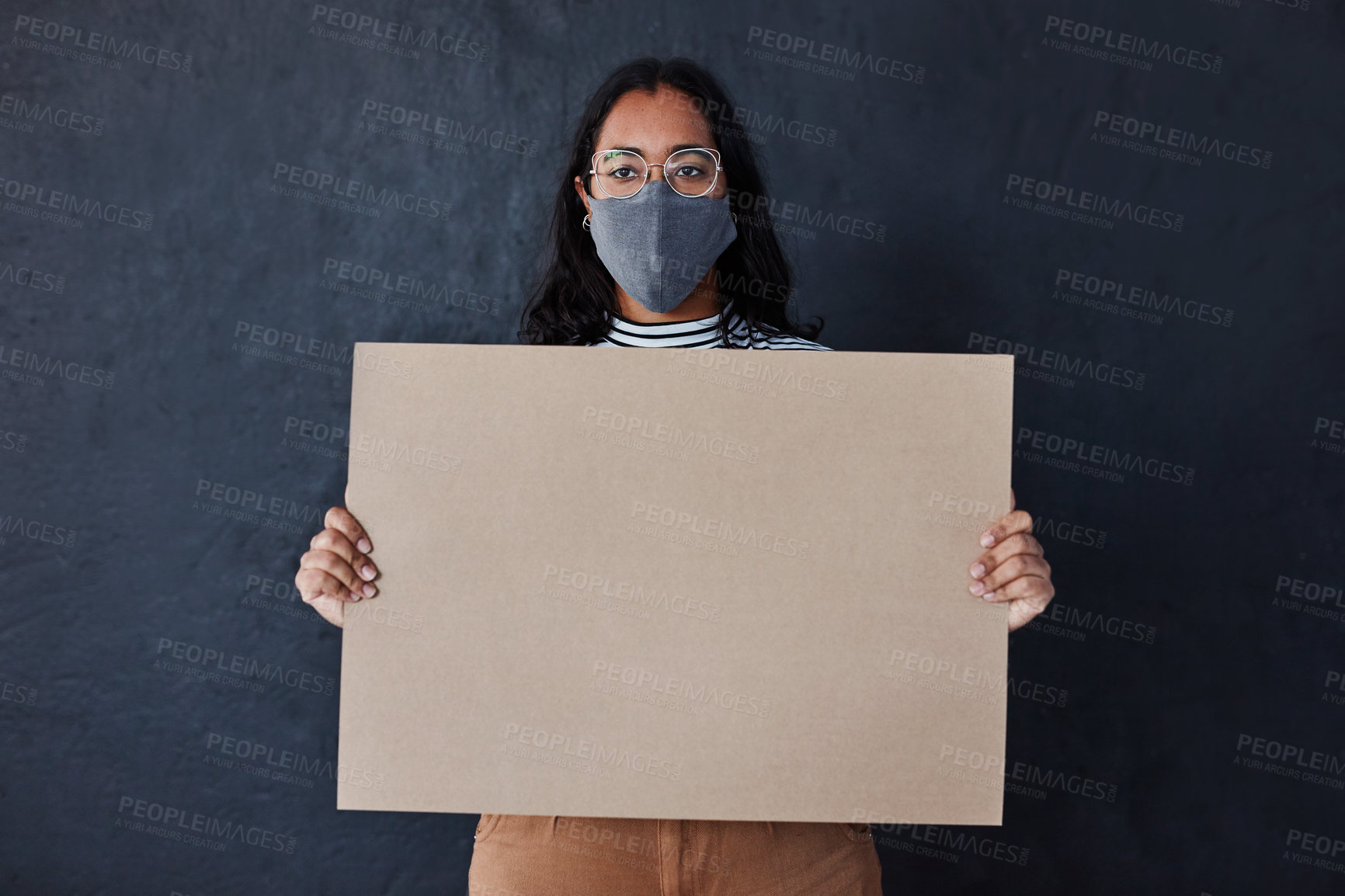 Buy stock photo Studio shot of a masked young woman holding a blank poster against a dark background