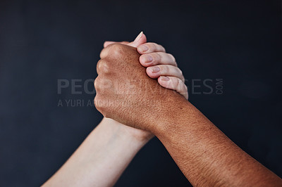 Buy stock photo Studio shot of two unrecognisable women joining hands against a dark background