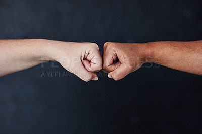 Buy stock photo Studio shot of two unrecognisable women bumping fists against a dark background