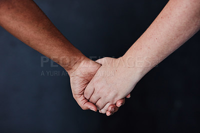 Buy stock photo Studio shot of two unrecognisable women holding hands against a dark background
