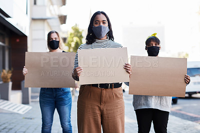 Buy stock photo Shot of a group of masked young women holding blank posters at a protest outdoors