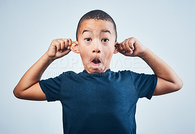 Buy stock photo Studio shot of a cute little boy playfully pulling his ears against a grey background