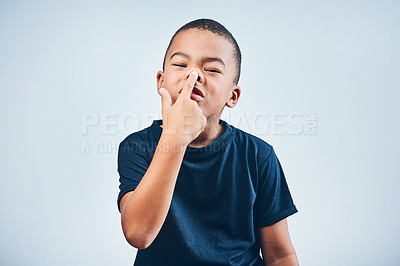 Buy stock photo Studio shot of a cute little boy playfully sticking up his nose against a grey background
