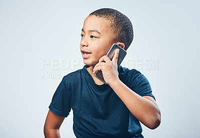 Buy stock photo Studio shot of a cute little boy using a smartphone against a grey background