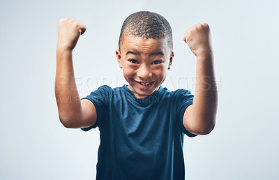 Buy stock photo Studio shot of a cute little boy flexing his muscles against a grey background
