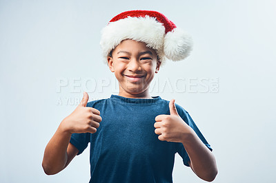 Buy stock photo Studio shot of a cute little boy wearing a Santa hat and showing thumbs up against a grey background