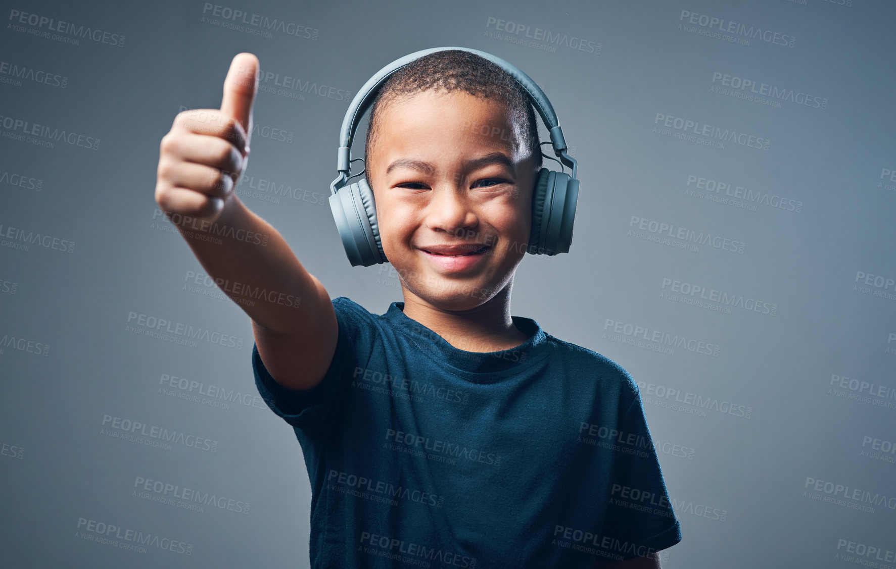 Buy stock photo Studio shot of a cute little boy using headphones and showing thumbs up against a grey background