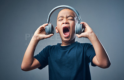 Buy stock photo Studio shot of a cute little boy using headphones with his mouth open against a grey background