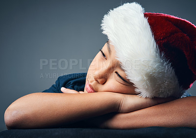 Buy stock photo Studio shot of a cute little boy wearing a Santa hat and looking thoughtful against a grey background