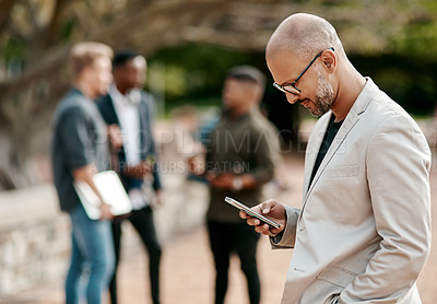 Buy stock photo Shot of a mature businessman using a smartphone against a city background