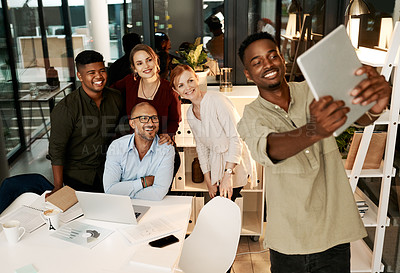 Buy stock photo Shot of a group of businesspeople using a digital tablet during a late night brainstorming session at work