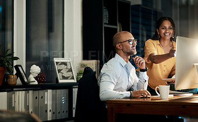 Buy stock photo Shot of a businessman and businesswoman using a computer during a late night at work