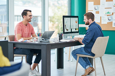Buy stock photo Shot of two young businessmen using their computers in a modern office