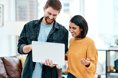 Buy stock photo Shot of a happy young couple using a laptop together at home