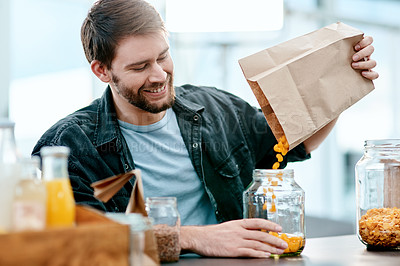 Buy stock photo Shot of a young man packing his groceries into glass containers after returning home from the store
