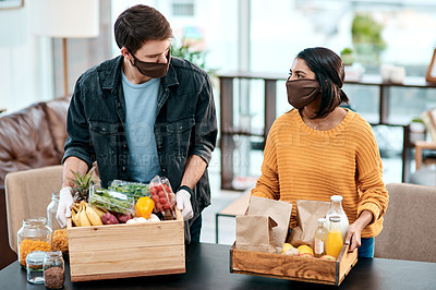 Buy stock photo Shot of a young couple wearing masks while unpacking their groceries at home