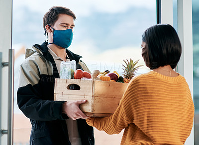 Buy stock photo Shot of a masked young man delivery fresh fruit and vegetables to a woman at home