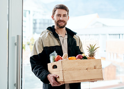 Buy stock photo Shot of a young man delivering fresh fruit and vegetables to a place of residence
