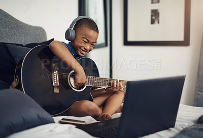 Buy stock photo Shot of a young boy wearing headphones while playing the guitar