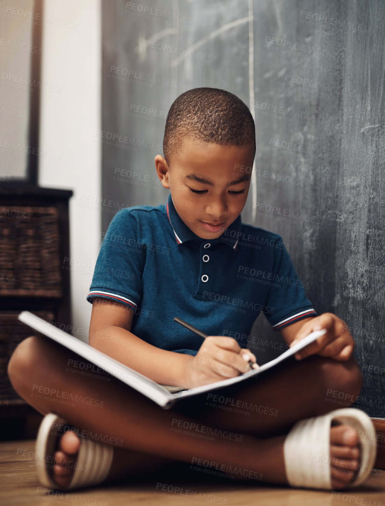 Buy stock photo Shot of a young boy writing in a book while sitting at home