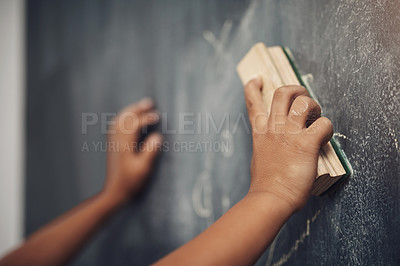 Buy stock photo Cropped shot of an unrecognizable boy using the duster to clean a blackboard