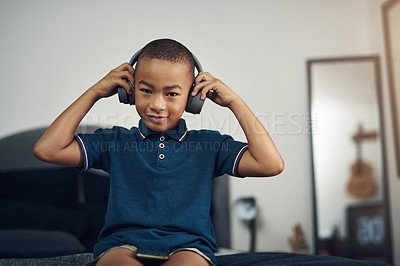 Buy stock photo Shot of a young boy listening to music through headphones while sitting at home