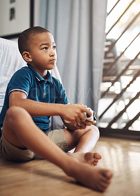 Buy stock photo Shot of a young boy playing video games at home