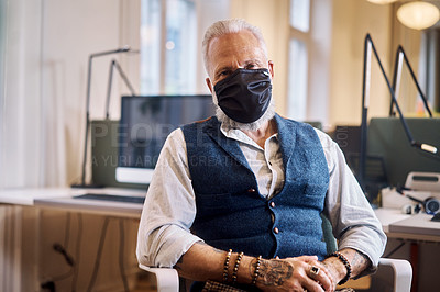 Buy stock photo Cropped portrait of a handsome mature businessman sitting in his office while wearing a mask