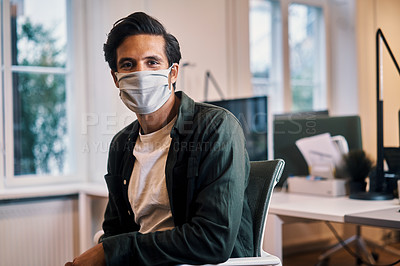 Buy stock photo Cropped portrait of a handsome young businessman sitting in his office while wearing a mask