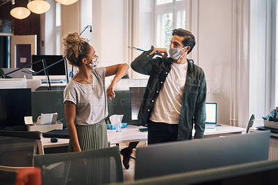 Buy stock photo Cropped shot of two young business colleagues greeting one another with an elbow bump in the office while wearing masks