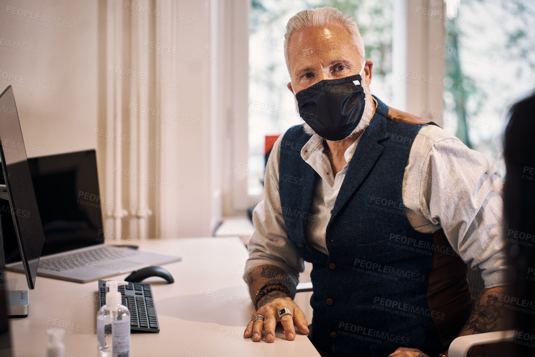 Buy stock photo Cropped shot of a handsome mature businessman wearing a mask while working in the office