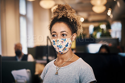 Buy stock photo Cropped shot of an attractive young businesswoman looking thoughtful while standing in her office wearing a mask