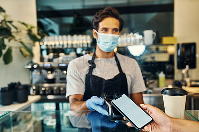 Buy stock photo Shot of a masked young man taking a phone payment from a customer in his cafe