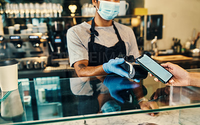 Buy stock photo Shot of a masked man taking a phone payment from a customer in his cafe