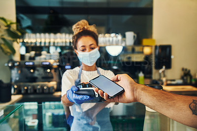 Buy stock photo Shot of a masked young woman taking a phone payment from a customer in her cafe
