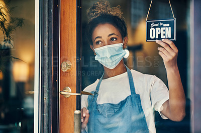 Buy stock photo Shot of a masked young woman hanging an open sign on the window of a cafe