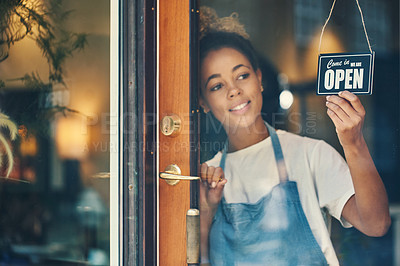 Buy stock photo Shot of a young woman hanging an open sign on the window of a cafe