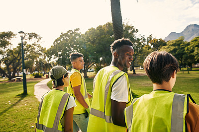 Buy stock photo Rearview shot of a group of young volunteers doing community service in their local park