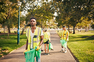 Buy stock photo Cropped portrait of a young male volunteer doing community service in the local park with his friends in the background