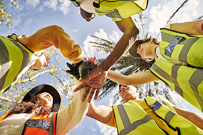 Buy stock photo Low angle shot of a group of young volunteers standing with their hands in a huddle while doing community service in their local park