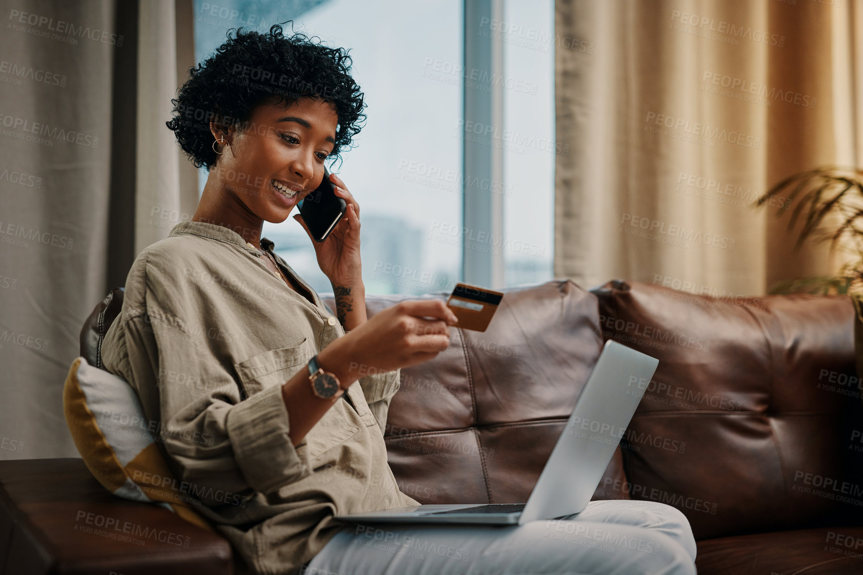 Buy stock photo Shot of a young woman looking at her credit card while talking on the phone and sitting with her laptop