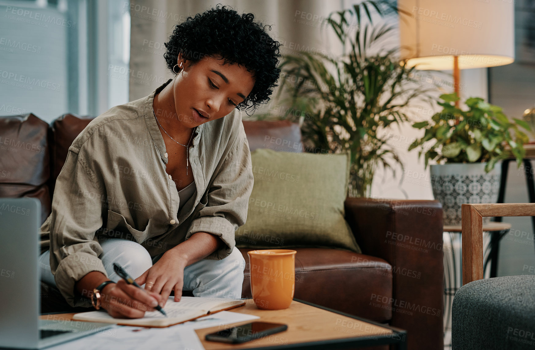 Buy stock photo Cropped shot of a beautiful young woman writing in her notebook while sitting at home