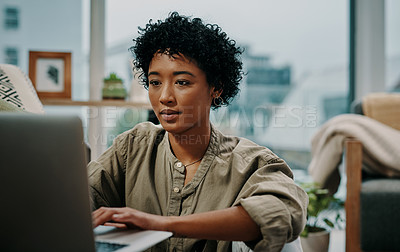 Buy stock photo Cropped shot of a young woman using her laptop while sitting at home