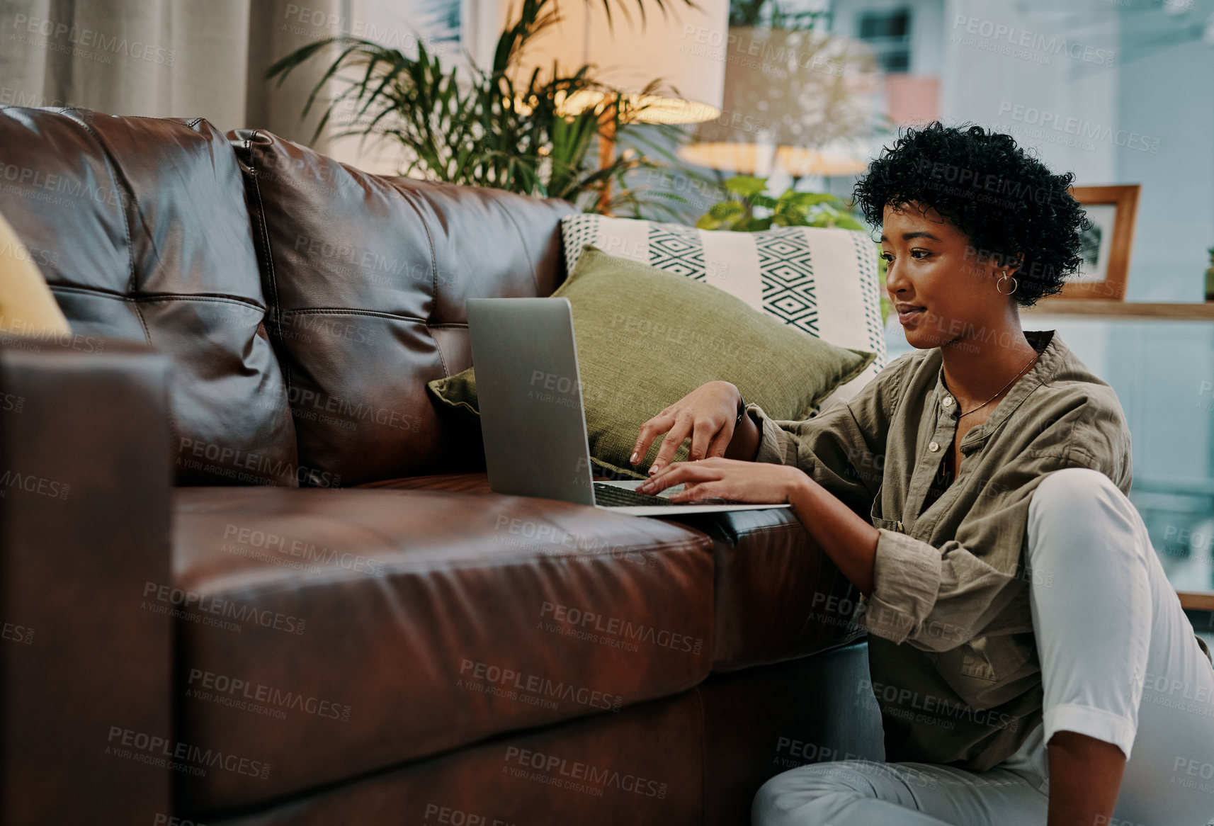 Buy stock photo shot of a young woman using her laptop while sitting at home