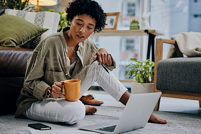 Buy stock photo Shot of a young woman having coffee while using her laptop at home