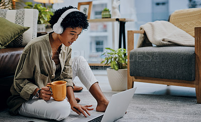 Buy stock photo Shot of a young woman wearing headphones while using her laptop and drinking coffee at home
