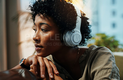 Buy stock photo Cropped shot of a young woman looking thoughtful while wearing headphones at home